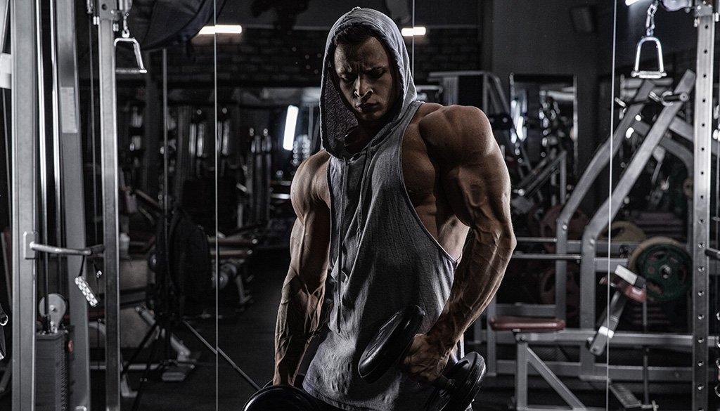 muscle man wearing hoodie in gym