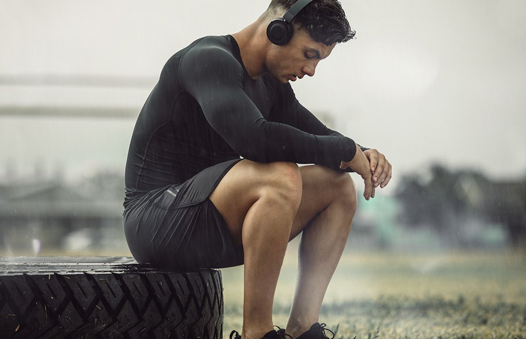 man post workout sitting on tire