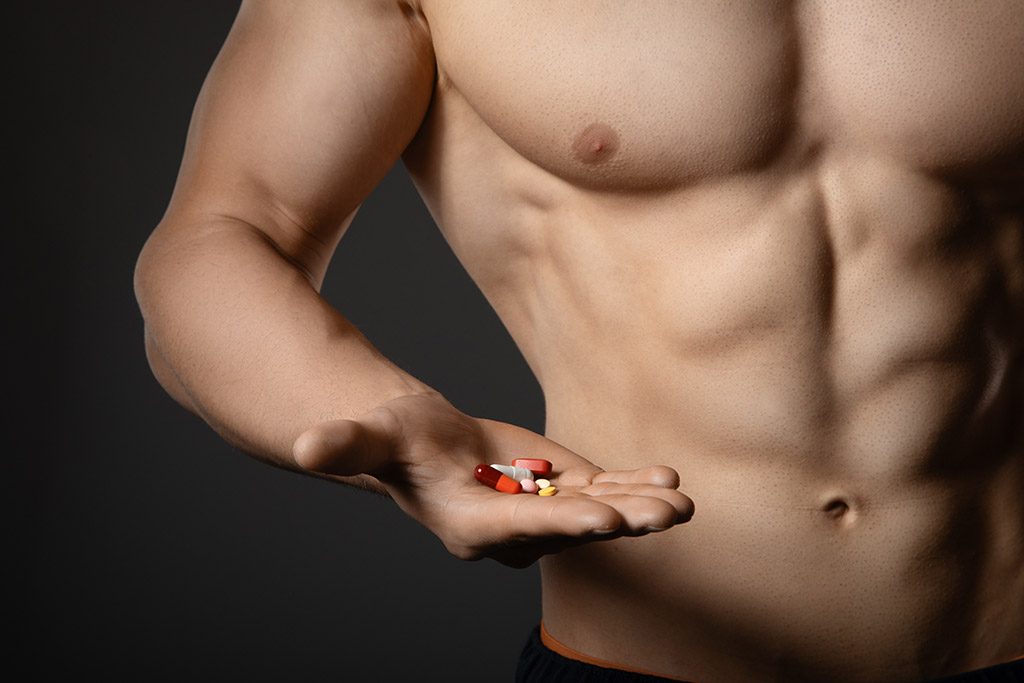 muscle man holding pills